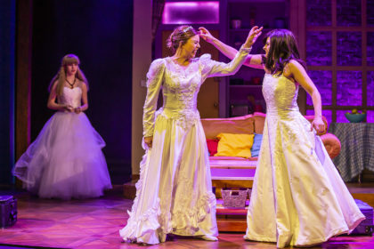Friendsical, two characters in wedding dresses flicking each others foreheads