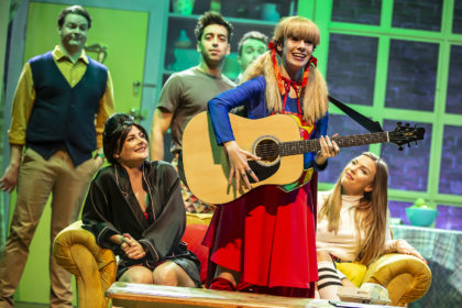 Friendsical, character playing Phoebe dressed in a Supergirl outfit playing the guitar and singing